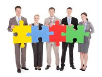 Confident business people holding colorful jigsaw puzzle Royalty Free Stock Photography