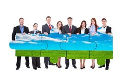 Confident business people joining nature jigsaw pieces. Full length portrait of confident business people joining nature jigsaw pieces against white background Stock Images