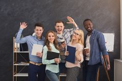 Confident business people with posing in office. Cheerful business people in office. Successful young team posing for photo, greeting and smiling at camera Royalty Free Stock Photo