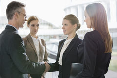 Confident business people shaking hands at workplace Royalty Free Stock Images