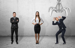 Confident business people standing straight and scared businessman shielding himself from the giant mechanical claw Royalty Free Stock Images
