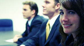 Confident business team. Two business men look confidently woman looks towards the camera Royalty Free Stock Photo