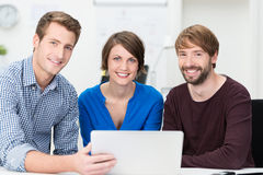 Confident business team grouped around a laptop. Confident young business team of two men and a women grouped around a laptop as they sit at a desk in the office