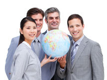 Confident business team looking at a globe Royalty Free Stock Photos