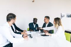 Confident business team of mixed ages and ethnicity making handshaking while meeting in a modern office. They are discussing ideas. A confident business team of royalty free stock images