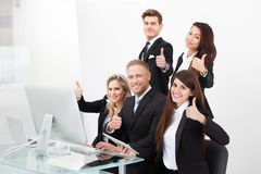 Confident business team showing thumbs up Stock Photo