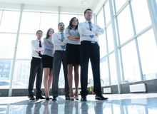 Smiling and confident business team standing in front of a bright Royalty Free Stock Image