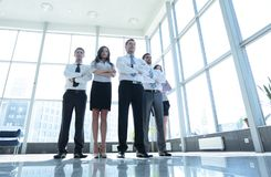 Smiling and confident business team standing in front of a bright Stock Images