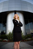 Confident business woman. Attractive blond business woman wearing professional business suit standing outside a modern office building with arms crossed royalty free stock images