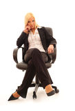 Confident Business Woman. Young confident business woman with blonde hair in a stylish dark suit on a white background royalty free stock photography