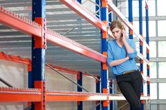 Confident business woman  on cellphone in warehouse Royalty Free Stock Images
