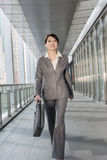 Confident business woman holding briefcase and walking Royalty Free Stock Photos