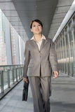 Confident business woman holding briefcase and walking Stock Photo
