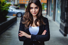Confident business woman looking at the camera. While standing on the street with hands crossed stock photo