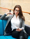 Confident business woman with phone in office Stock Photo