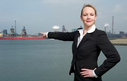 Confident business woman pointing finger at ships in the harbor Royalty Free Stock Photography