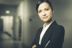 Confident business woman smiling with arms crossed Stock Image