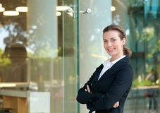 Confident business woman smiling by glass window. Portrait of a confident business woman smiling by glass window outside office building Stock Image
