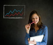 Confident business woman or teacher with notepad and pen against a blackboard with graph chart Stock Photography