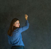 Woman writing on dark blackboard background Royalty Free Stock Image