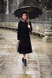 Confident business woman with umbrella. Confident business woman dressed in trenchcoat with umbrella Stock Photo