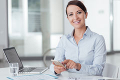 Confident business woman using a smart phone. Confident businesswoman in the office using a touch screen smart phone and smiling at camera Stock Photos
