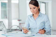 Confident business woman using a smart phone Stock Photo