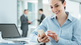Confident business woman using a smart phone. Confident smiling business woman sitting at office desk and using a smart phone, business people standing on Royalty Free Stock Photos