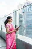 Confident business woman using a tablet PC outdoors. Confident business woman using a tablet PC while wearing traditional Indian clothing outdoors Royalty Free Stock Image