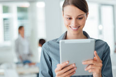 Confident business woman using a touch screen tablet stock photo
