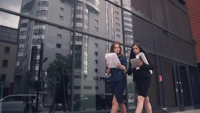 Confident business woman walking in the background of a modern business center. girl holding blueprints and talking on stock video