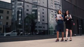 Confident business woman walking in the background of a modern business center. girl holding blueprints and talking on stock footage