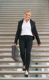 Confident business woman walking downstairs with briefcase Stock Photos
