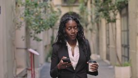 Confident business woman walks street. Natural afro american beauty business woman in stylish outfit for office work, walks on street with take away coffee cup stock video