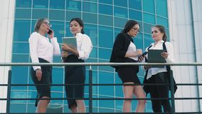 Confident business women doing business outdoors. They talk to each other standing in pairs stock footage