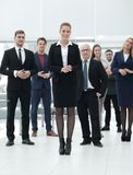 Confident business woman standing in front of his business team. Royalty Free Stock Images