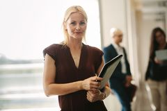 Confident business woman standing in office Stock Image