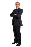 Confident businessman. Wearing a suit standing with his arms folded Royalty Free Stock Photos