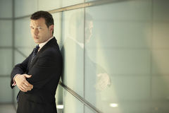 Confident Businessman With Arms Crossed Leaning On Glass Wall Stock Photography