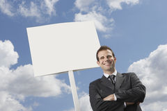 Confident businessman with arms crossed standing by blank sign against cloudy sky Royalty Free Stock Images