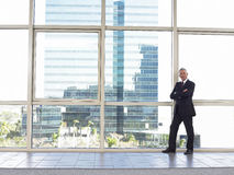 Confident Businessman With Arms Crossed Standing By Window Royalty Free Stock Photo