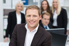 Confident businessman backed by his team royalty free stock image