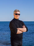 Confident businessman in black posing on the seashore. Confident handsome middle-aged man in black wearing sunglasses posing with his arms crossed on the Royalty Free Stock Photography
