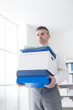 Confident businessman carrying boxes Royalty Free Stock Images