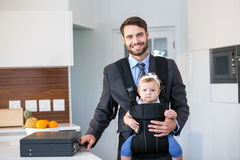Confident businessman carrying daughter by table Royalty Free Stock Images