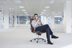 Confident Businessman On Chair In New Office. Full length of confident young businessman on chair in empty office space Stock Photos