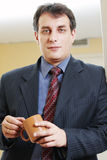 Confident businessman with cup Stock Photos