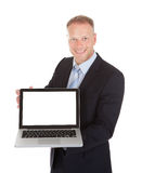 Confident Businessman Displaying Laptop Over White Background stock photo