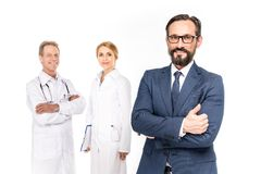 confident businessman showing thumb up and smiling at camera while doctors standing behind royalty free stock photos