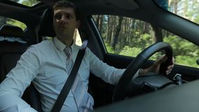 Confident businessman driving car in countryside stock footage